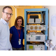 Lead researchers Drs. Martin Reinhardt and Susanne Votruba stand next to the carbon dioxide and oxygen analyzers, and outside the whole-room indirect calorimeter.