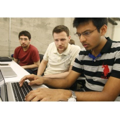 Shiva Gopalan, a computer engineering masters student at Texas A&M University(far right), confers with IBM developers Henrique Copelli Zambon (center) and Luiz Aoqui, during an IBM hosted Spark Hackathon at Galvanize. (Credit:George Nikitin)