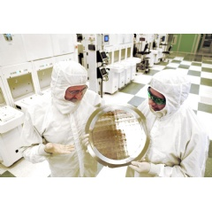 Dr. Michael Liehr (left) of SUNY Polytechnic Institute's Colleges of Nanoscale Science and Engineering and Bala Haran (right) of IBM Research inspect a wafer comprised of 7nm (nanometer) node test chips in a clean room. (Credit: Darryl Bautista)