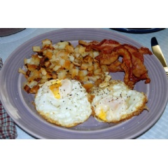 Breakfast plate of fried foods - bacon, eggs, and hashbrowns.(Credit: American Heart Association)