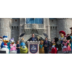 Walt Disney World President George A. Kalogridis, surrounded by a flurry of beloved Disney characters, addresses Magic Kingdom Park guests during the 45th anniversary of Walt Disney World, Saturday, Oct. 1, 2016.