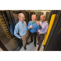 Sandia National Labs' Roger Suppona, left, and John Naegle, center, and Lewis Rhodes Labs CEO David Follett examine their Neuromorphic Cyber Microscope. This small processor can replace racks of conventional cybersecurity systems. Photo Randy Montoya