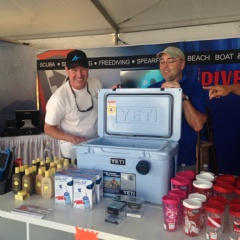 Divers Direct staff member, Tim, showing an excited customer our new line of Yeti Coolers at the Fort Lauderdale International Boat Show.