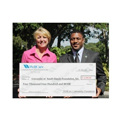 WellCare�s chief pharmacy officer, Laura Hungiville, presents Dr. Kevin Sneed, dean of the college of pharmacy, University of South Florida, with $4,400 to fund the college�s White Coat Ceremony.