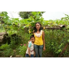 Mary Jane Lagarel Suco, with one of her sons, started to grow vegetables soon after Typhoon Haiyan wiped out her home garden in Leyte province, the Philippines