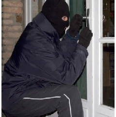 Burglar breaking into a home.