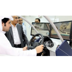 Abdullah A. Ghabbani and Salem A. Shehry observe as a Summer Enrichment Program student tests his skills in a driving simulator at Abqaiq's Industrial Training Center.