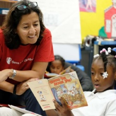 Janti Soeripto, president and chief operating officer of Save the Children U.S., reads with second grader Kaliya at one of Save the Children's literacy programs in Tennessee.