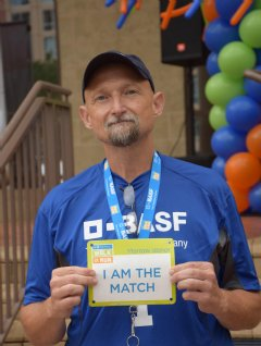 "BASF employee, Kelly Brooks, proudly holds his ""I am a Match"" sign at the awards ceremony for the Be The Match Walk +Run."