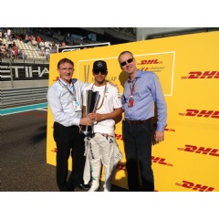 Ken Allen, CEO, DHL Express (left) and Arjan Sissing, SVP, Corporate Brand Marketing, Deutsche Post DHL (right) hand the trophy to Lewis Hamilton before the 2014 FORMULA 1 ETIHAD AIRWAYS ABU DHABI GRAND PRIX.