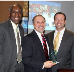 Carlton Daniels, chair of the board of directors of Habitat for Humanity Newark (left), and Jeffrey Farrell, executive director of the organization (at right), Sam Delgado, vice president of external affairs for Verizon New Jersey.