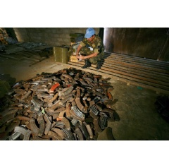 A UN peacekeeper in the Democratic Republic of the Congo (DRC) examines AK-47 magazines stored in a warehouse in Beni after they have been collected in the demobilization process in Matembo, North Kivu. UN Photo/Martine Perret