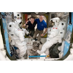 Astronauts (from left) Anne McClain and David Saint-Jacques are pictured in between a pair of spacesuits that are stowed and serviced inside the Quest airlock where U.S. spacewalks are staged.