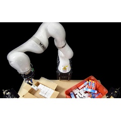 A robotic arm tightly packs items into a box for shipment.